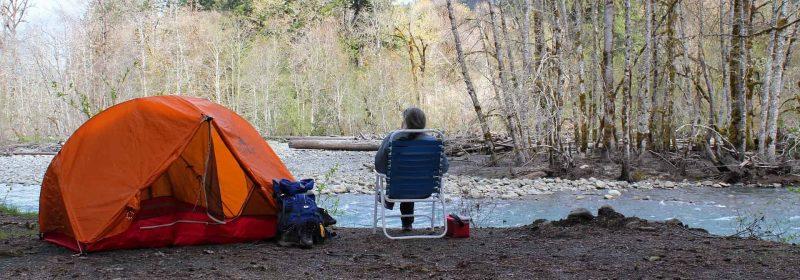 Camper sitzt auf Stuhl neben seinem Zelt