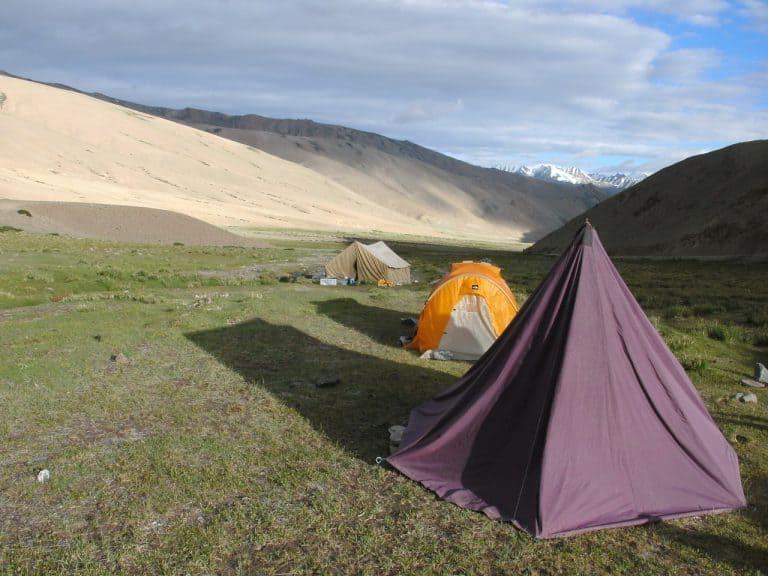 Zelte auf offener Wiese zwischen Bergen