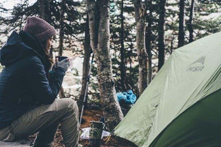 Wanderer mit Getränk vor Zelt