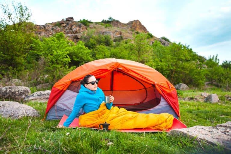 Frau in Schlafsack vor Zelt