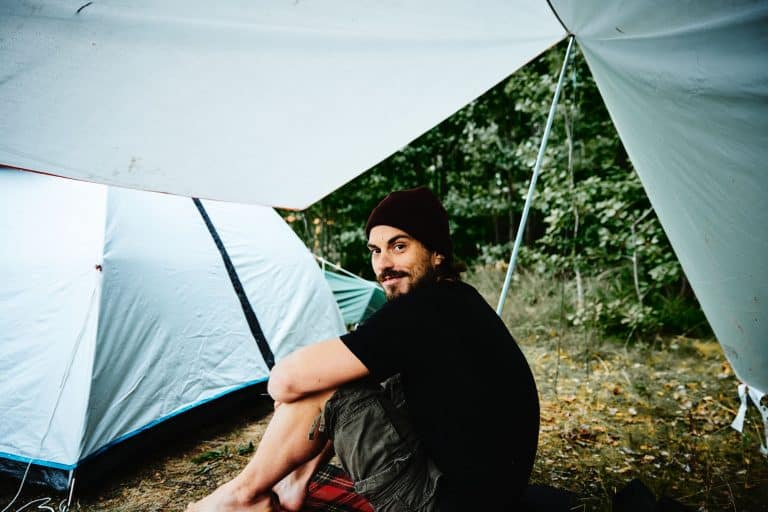 Mann unter Zeltplane