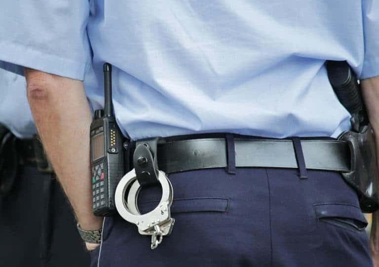 Polizist mit Funkgerät und Handschellen