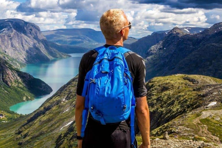 Mann trägt beim Wandern blauen Rucksack