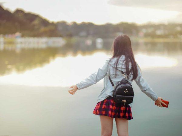 Frau mit kleinem Rucksack steht am Wasser