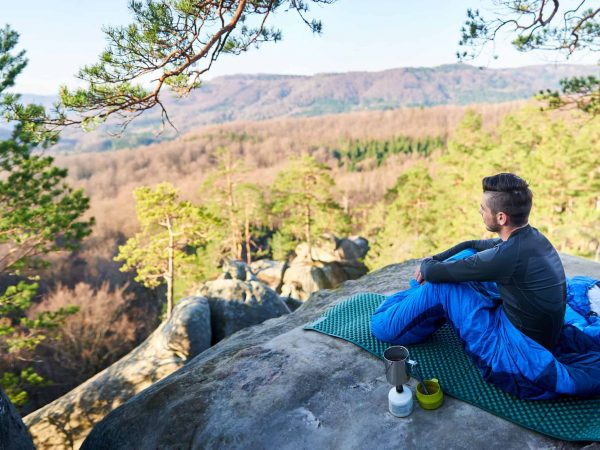 Young tourist, bearded handsome man sitting alone in sleeping bag on big rock having coffee and enjoying beautiful mountain view on clear sunny summer morning. Tourism and active lifestyle concept.