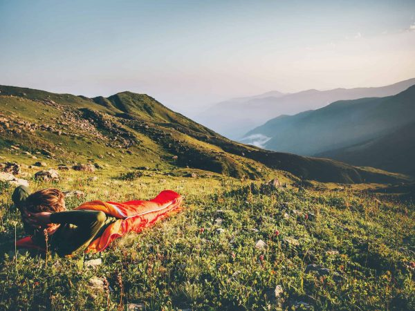Man relaxing in sleeping bag enjoying sunset mountains landscape Travel Lifestyle camping concept adventure summer vacations outdoor hiking mountaineering