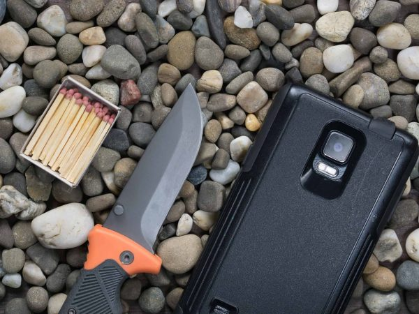 nowadays modern survival kit. box with matches, folding knife and rugged tough smartphone on rocks. always stay connected