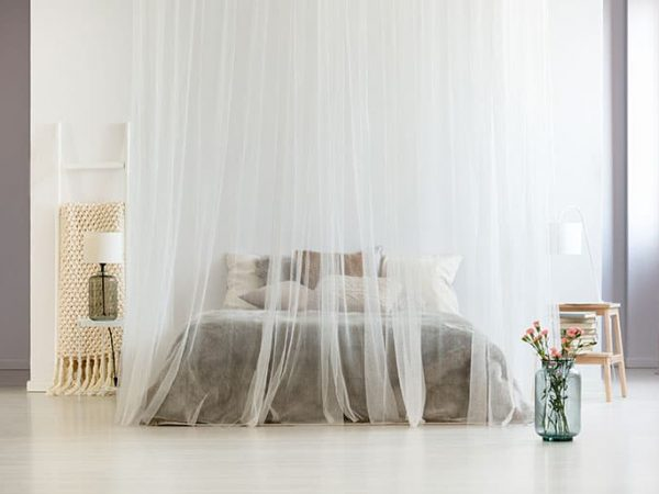 Modern homely bedroom interior in calm neutral colors with canopy over king-size bed and glass vase with flowers