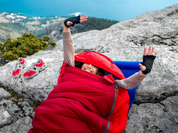 Young woman waking up in red sleeping bag on the rocky mountain