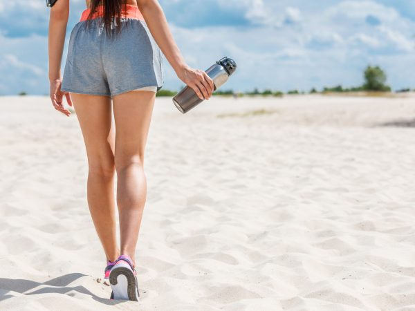 cropped back view of slim sportswoman with sport bottle