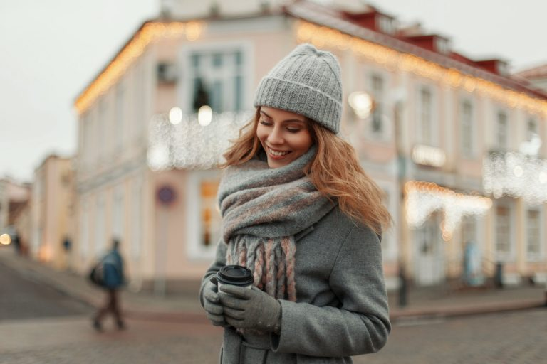Happy beautiful girl in a fashion vintage coat with a knitted st