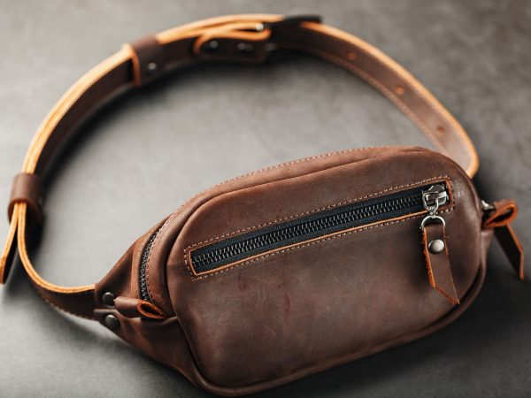 Handmade genuine brown leather on a dark background Brown belt bag. Elegant brown bag with a zipper. Banana bag