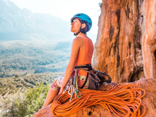 Climber sits near the rope and prepares to overcome the route. Slender girl holds climbing equipment. A woman in a helmet on the background of beautiful mountains. Rest after climbing.