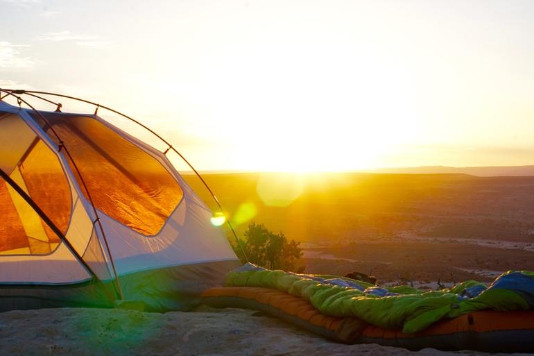 Ein idyllisches Bild bei Sonnenaufgang mit Schlafsack und aufgestelltem Zelt.