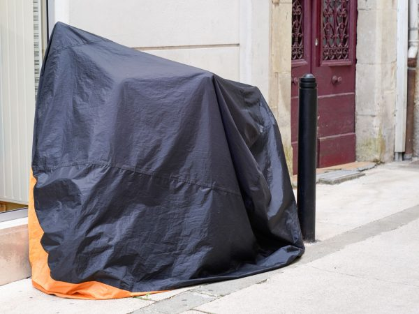 motorbike protected by protective cover in street motorcycle with dark grey orange tarpaulin jacket